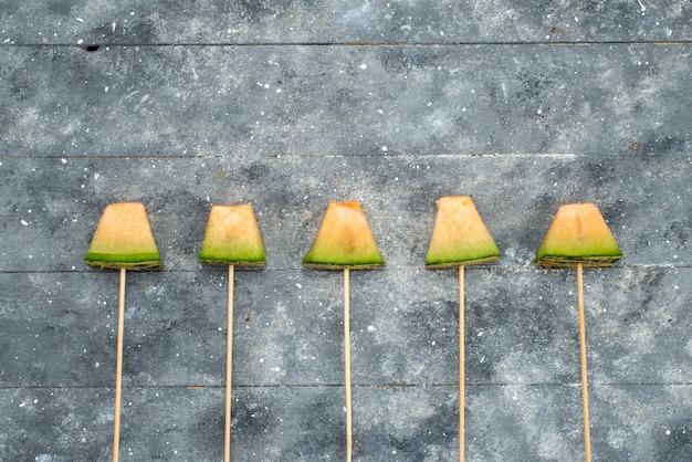 Melone vista dall'alto su bastoncini verdi e succosa morbida foderata in grigio