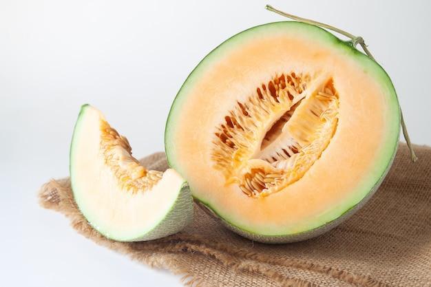 Meloni d'arancia metà e affettati su priorità bassa bianca. frutta sana