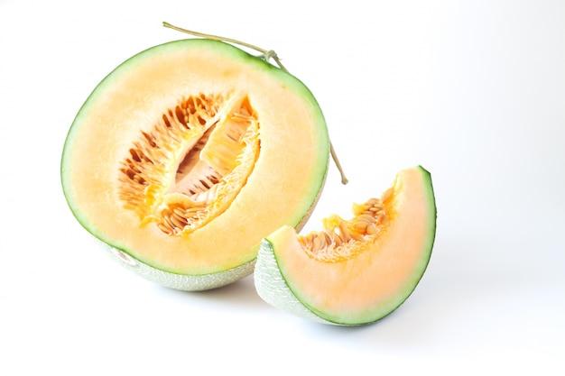 Meloni giapponesi a metà e affettati isolati su fondo bianco. frutta sana