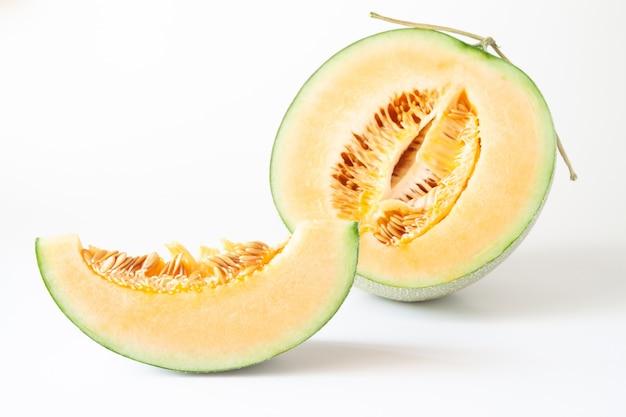 Meloni giapponesi a metà e affettati isolati su fondo bianco