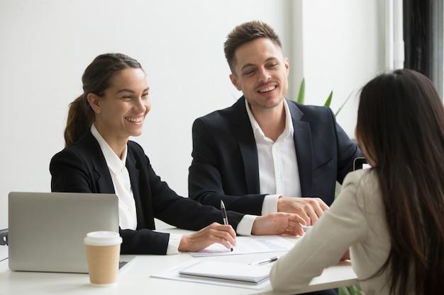 Membri del team amichevole chiacchierando ridere insieme durante la pausa ufficio
