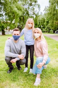 Membri della famiglia che si abbracciano, sorridendo alla telecamera indossando maschere di stoffa.