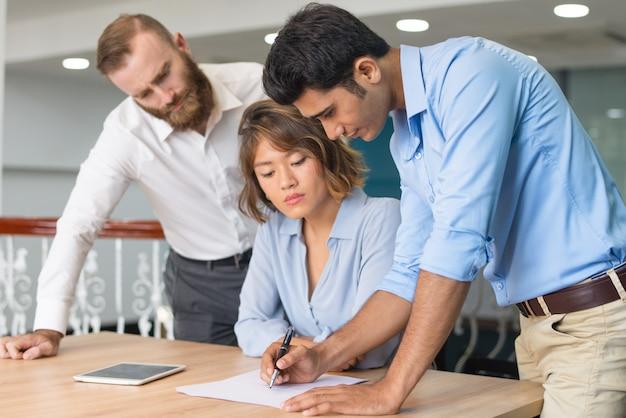 Membro del team creativo che condivide idee con due colleghi