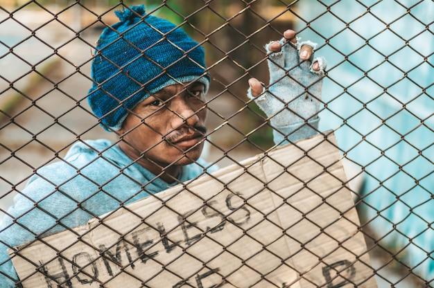 Mendicanti che si attaccano alla griglia con messaggi di senzatetto per favore aiutatemi.