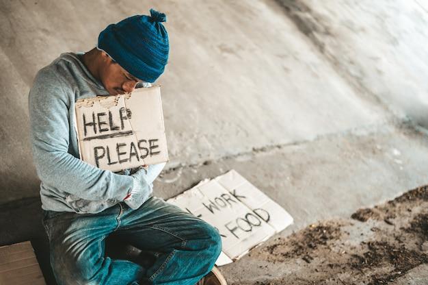 Mendicanti seduti sotto il ponte con un cartello, aiutano per favore.