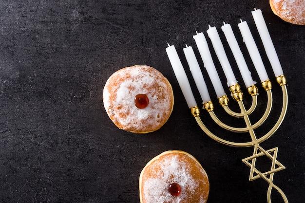 Menorah ebraica di hanukkah e ciambelle di sufganiyot sul nero vista dall'alto copia spazio