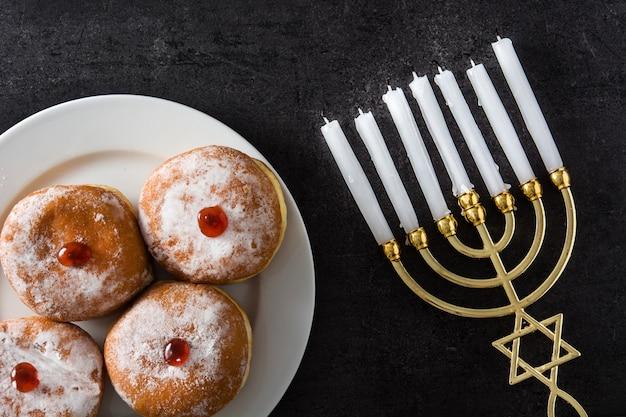 Menorah ebraica di hanukkah e ciambelle di sufganiyot sul nero