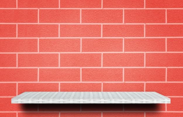 Mensola bianca vuota sul fondo del mattone rosso per l'esposizione del prodotto