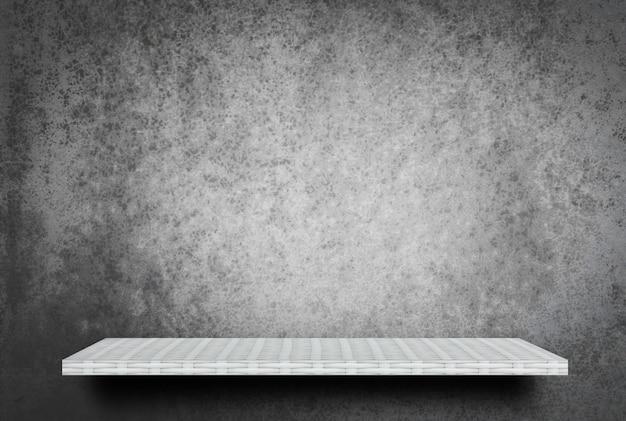 Mensola bianca vuota sul fondo grigio della parete del cemento per l'esposizione del prodotto