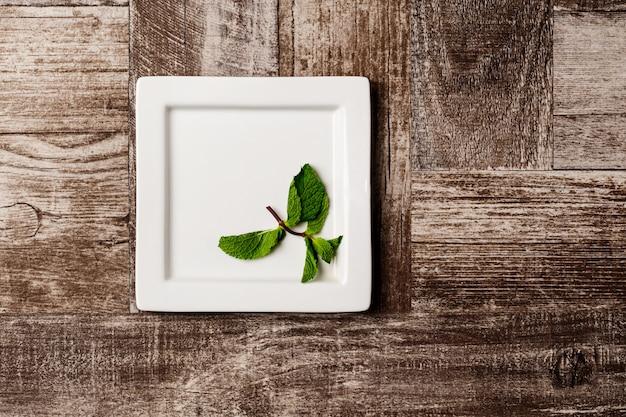 Menta sul piatto bianco su legno