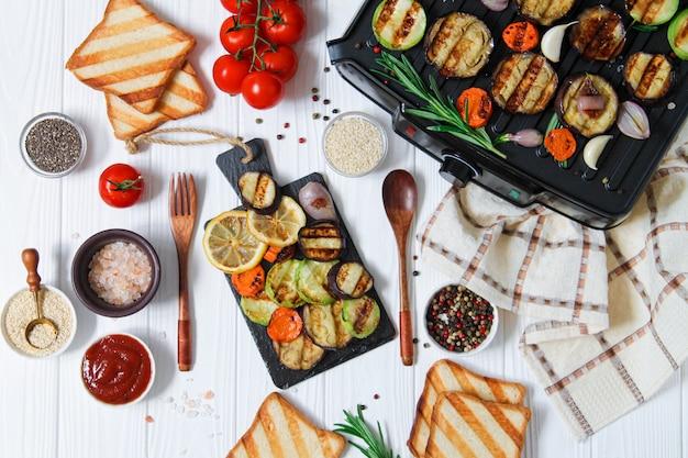 Menu alla griglia vegetariano equilibrato con pane sano barbecue e verdure calde (zucchine, melanzane, carota, limone) su fondo di legno bianco vista dall'alto