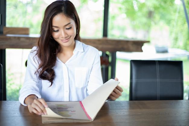 Menu aperto della donna asiatica per ordinare nel caffè e nel ristorante del caffè e sorridere per il tempo felice