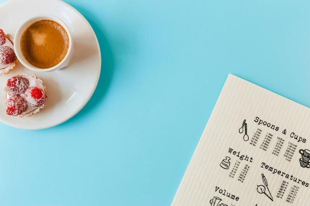 Menu; crostata di frutta fatta in casa e tazza di caffè sul piatto sopra lo sfondo blu