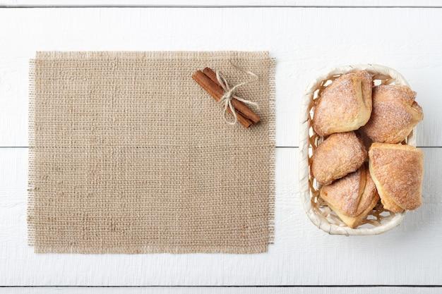 Menu di concetto - tortini casalinghi con cannella e tela di sacco su un fondo di legno bianco con lo spazio della copia.