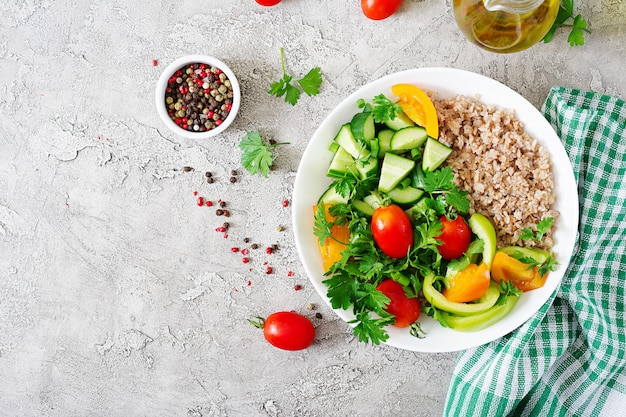 Menu dietetico. insalata vegetariana sana degli ortaggi freschi - pomodori, cetriolo, peperoni dolci e porridge sulla ciotola. cibo vegano. disteso. vista dall'alto