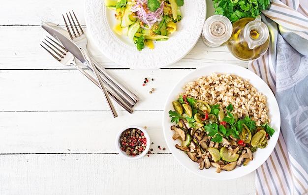 Menu dietetico. pasto vegetariano sano - funghi shiitake, zucchine e porridge di farina d'avena sulla ciotola. cibo vegano. disteso. vista dall'alto