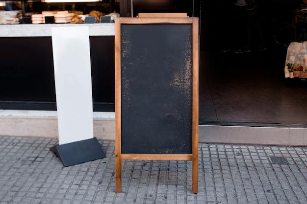 Menu lavagna vuota e cartellone bianco davanti al ristorante in strada