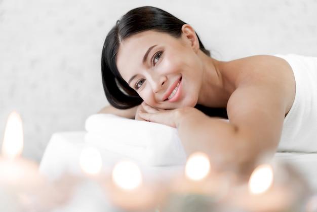 Menzogne di rilassamento di bello trattamento della pelle di bellezza della giovane donna sull'asciugamano nel salone della stazione termale e di massaggio