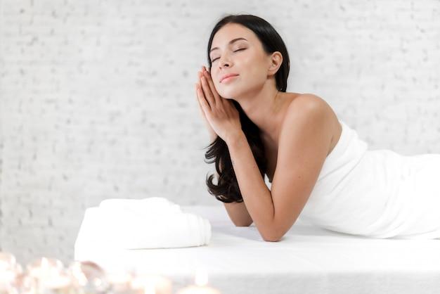 Menzogne di rilassamento di bello trattamento di bellezza della pelle della giovane donna sull'asciugamano nel salone della stazione termale e di massaggio
