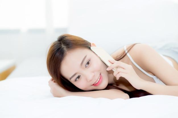 Menzogne sorridente della bella donna asiatica e si rilassi sul letto.