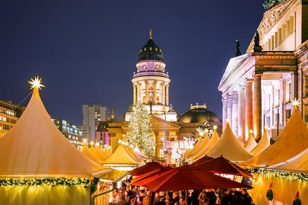 Mercatino di natale illuminato sulla piazza gendarmenmarkt di notte a berlino, germania
