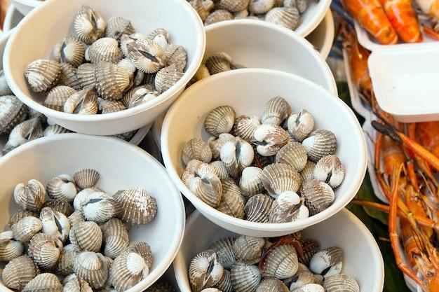 Mercato del pesce tailandese. molluschi crudi sul piatto.