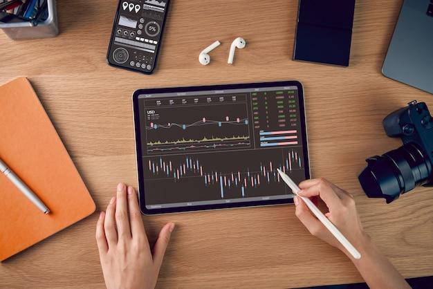 Mercato di borsa, commerciante dell'uomo d'affari che guarda sulla compressa con la linea della candela di analisi dei grafici nella stanza dell'ufficio, diagrammi sullo schermo.