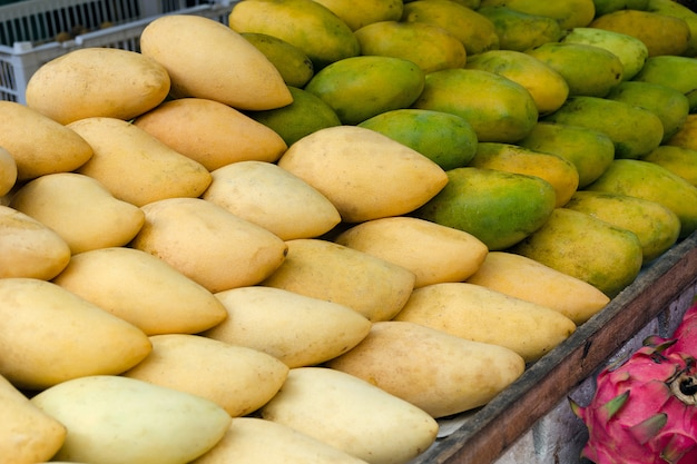 Mercato di frutta con mango maturo.