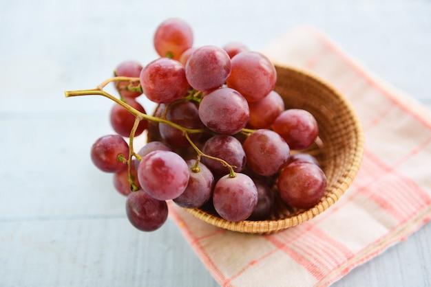 Merce nel carrello del mazzo dell'uva rossa su di legno