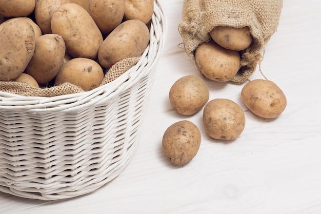 Merce nel carrello delle patate su bianco di legno