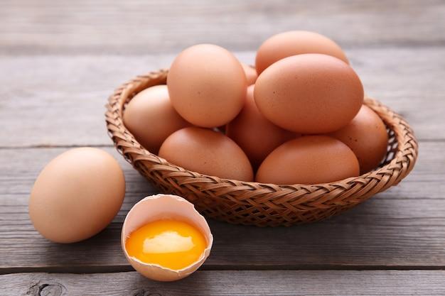 Merce nel carrello delle uova del pollo su fondo di legno grigio