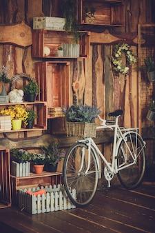 Merce nel carrello di plastica falsa dei fiori sulla retro bicicletta bianca