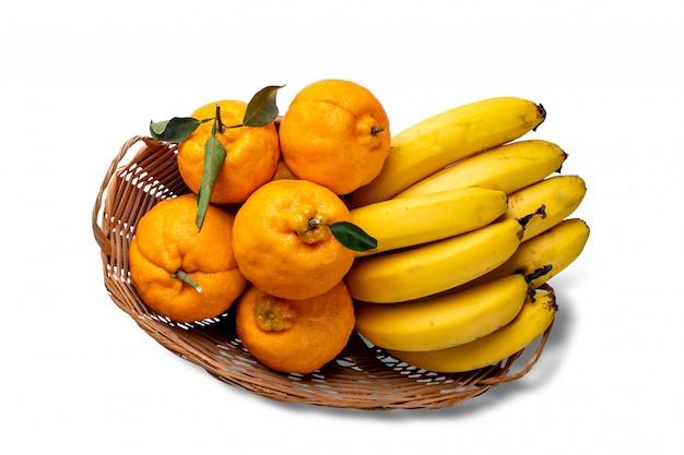 Merce nel carrello di ponkas delle banane e dei mandarini, isolata su fondo bianco.