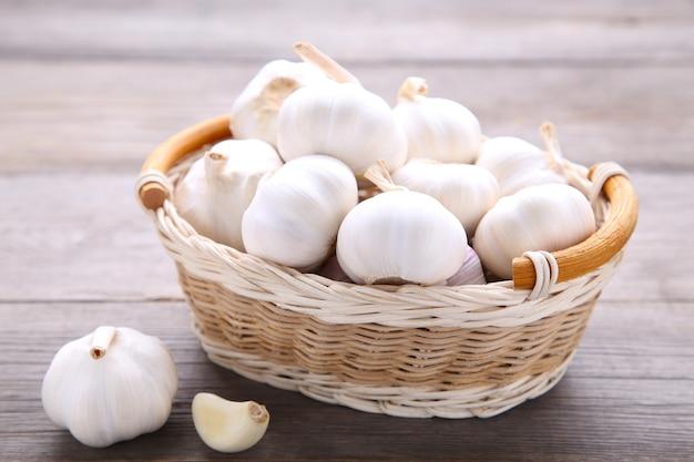 Merce nel carrello fresca dell'aglio su un fondo di legno grigio