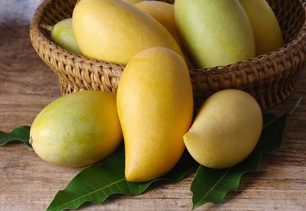 Merce nel carrello matura della frutta dei manghi con le foglie su di legno