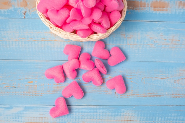 Merce nel carrello rosa della decorazione di forma del cuore sul fondo di legno blu della tavola. amore, matrimonio, romantico e felice concetto di vacanza di san valentino