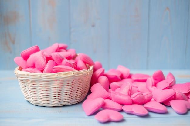Merce nel carrello rosa della decorazione di forma del cuore sul fondo di legno blu della tavola