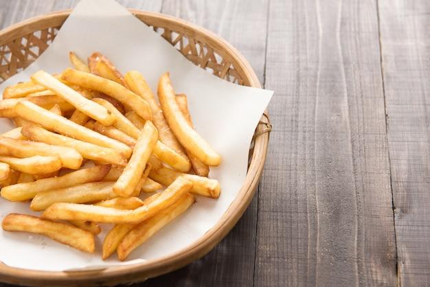 Merce nel carrello tradizionale delle patate fritte su fondo di legno