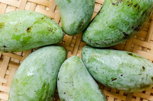Merce nel carrello verde fresca dei manghi sulla tavola di legno