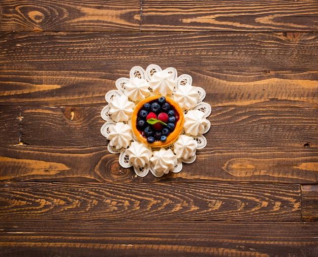 Meringa bianca dolce e altri componenti su un fondo di legno