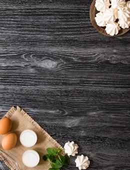 Meringa bianca dolce e altri componenti su una superficie di legno, spazio libero per il testo.