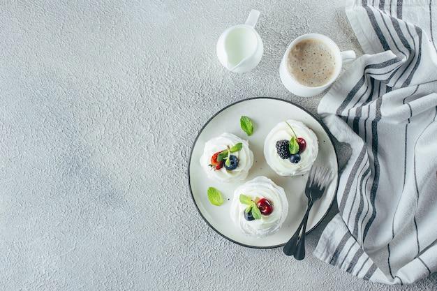 Meringa dessert pavlova con bacche fresche su un piatto.