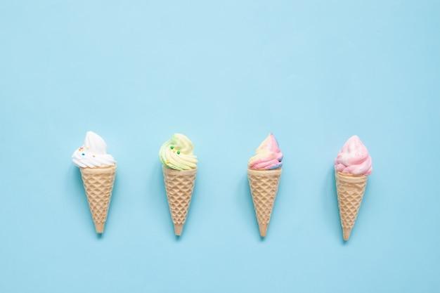 Meringa pastello sui coni gelati su fondo blu