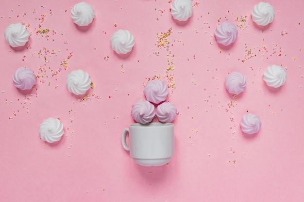 Meringhe bianche e rosa intrecciate in una ciotola di porcellana e picchi colorati sul rosa