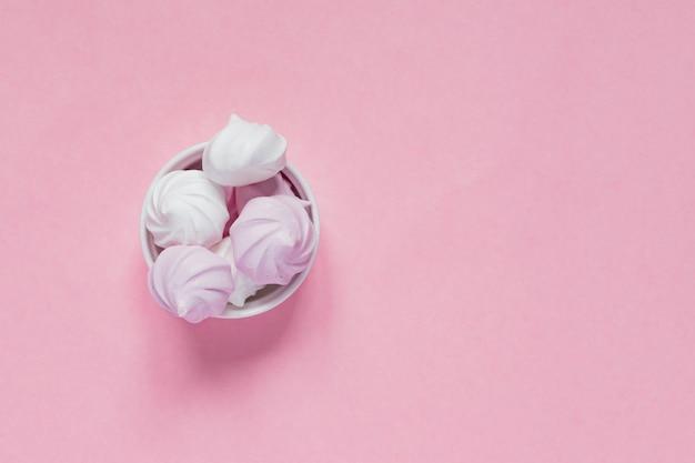 Meringhe bianche e rosa ritorte in una ciotola di porcellana su rosa
