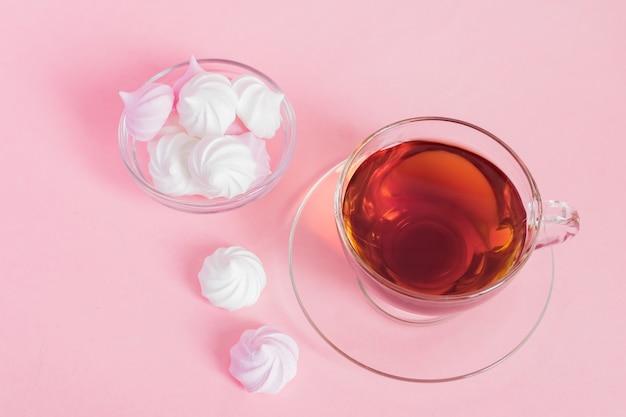 Meringhe contorte bianche e rosa e tazza di tè sul rosa