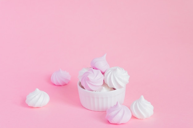 Meringhe contorte bianche e rosa in ciotola della porcellana su fondo rosa, cartolina d'auguri, spazio della copia