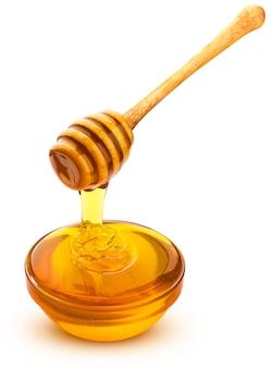 Merlo acquaiolo del miele e ciotola di miele di versamento su superficie bianca