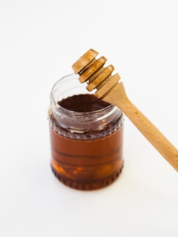 Merlo acquaiolo del miele sulla fine del barattolo su