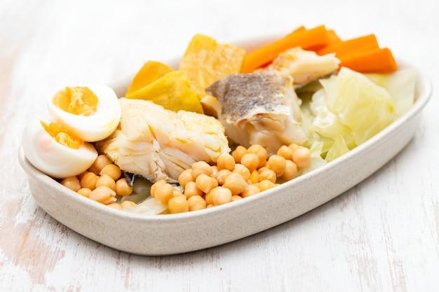Merluzzo bollito con le verdure bollite sul piatto